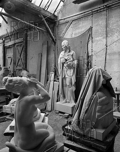 Roger-Viollet | 508161 | World War II. German occupation. Statues in a warehouse. At the centre, statue of Voltaire (1694-1778), French writer, nowadays in the Champion park (VIth arrondissement). Paris, 1941. | © Pierre Jahan / Roger-Viollet