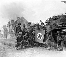 Roger-Viollet | 882312 | World War II. Lined up in front of a wrecked German tank and displaying a captured swastika, is a group of Yank infantrymen who were left behind to