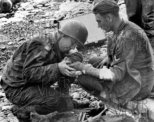 Roger-Viollet | 705128 | World War II. Normandy landings. Doctor of the U.S. Army tending a German prisoner on Omaha Beach (France), on June 6, 1944. | © Roger-Viollet / Roger-Viollet