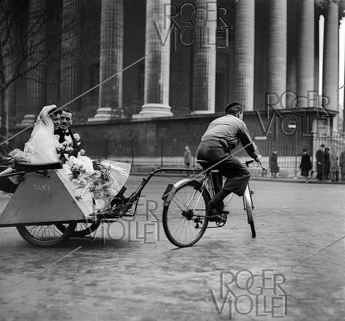Roger-Viollet | 166549 | World War II. Wedding on a cycle taxi, at the place de la Madeleine. Paris, December 1941. | © LAPI / Roger-Viollet