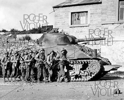 Roger-Viollet | 497369 | World War II. Yanks of 60th inf. regt advance into a Belgian town under the protection of a heavy tank. September 9, 1944. | © US National Archives / Roger-Viollet