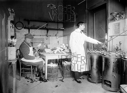 Roger-Viollet | 911453 | World War One. Laboratory of the french army dedicated to typhus vaccines. Sterilising the siphons used to place the vaccine in dishes. Val-de-Grâce hospital. Paris, 1916.$$$ | © Jacques Boyer / Roger-Viollet