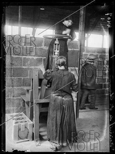 Roger-Viollet | 513092 | World War One. Visit of Emile Rimailho (1864-1954), French Colonel, at the Saint-Chamond steelworks (France), August 1915. Woman assemblying shells for 75mm field guns. Photograph published in the newspaper  Excelsior  of Sunday, August 15, 1915. | © Piston / Excelsior - L'Equipe / Roger-Viollet