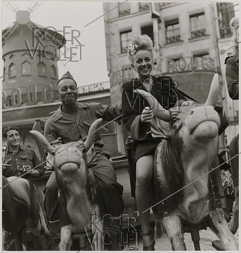 Roger-Viollet | 832669 | Young woman and US soldiers on a merry-go-round in front of the Moulin Rouge, place Blanche. Paris (IXth arrondissement), 1945. Photograph by Roger Schall (1904-1995). Paris, musée Carnavalet. | © Roger Schall / Musée Carnavalet / Roger-Viollet
