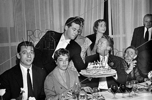 Roger-Viollet | 995546 | Yves Montand, Simone Signoret, Charles Trenet and his mother, Annie Cordy (standing), celebrating Charles Trenet's birthday at the restaurant of the Eiffel Tower (1955). | © Roger-Viollet / Roger-Viollet