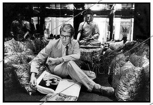 Roger-Viollet | 1376383 | Yves Saint-Laurent (1936-2008), French top designer and businessman, at his house, rue de Babylone, surrounded by his personal items. Paris (VIIth arrondissement), 1977. Photograph by André Perlstein (born in 1942). | © André Perlstein / Roger-Viollet