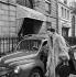 Lucky, mannequin français, dans sa Renault 4CV devant l'immeuble de Christian Dior. Paris, années 1950. © Jacques Rouchon/Roger-Viollet