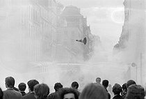 """Events of May-June 1968. Throwing of projectiles during the first confrontations between police forces and studens, rue Saint-Jacques. Paris (Vth arrondissement), on May 6, 1968. Photograph by Jacques Boissay and Bernard Charlet, from the collections of the French newspaper """"France-Soir"""". Bibliothèque historique de la Ville de Paris. © Boissay,Charlet / Fonds France-Soir / BHVP / Roger-Viollet"""