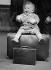 Départ en vacances. Bébé assis sur une valise, vers 1930. © Imagno/Roger-Viollet