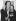 """Andy Warhol (1928-1987), artiste et cinéaste américain, et Madame Sackler lors du vernissage de l'exposition """"The American Indian Series"""" à la Ace Gallery. Paris, 1976. © Jack Nisberg / Roger-Viollet"""