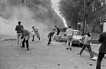 """Events of May-June 1968. Throwing of cobblestones during confrontations between the police forces and demonstrators, boulevard Saint-Germain. Paris (Vth arrondissement), on May 6, 1968. Photograph by Jacques Boissay and Bernard Charlet, from the collections of the French newspaper """"France-Soir"""". Bibliothèque historique de la Ville de Paris. © Boissay,Charlet / Fonds France-Soir / BHVP / Roger-Viollet"""