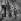 Deux immigrés marchent dans une rue commerçante. Photographie de Janine Niepce (1921-2007). © Janine Niepce / Roger-Viollet