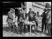 "World War One. Pilot of the Paris-Saint-Nazaire new airmail service. Etienne Clémentel, French politician, signing the statement in the presence of the Colonel Renard, Mr Esnault-Pelterie and Mr D'aubigny. Le Bourget (France), on August 17, 1918. Photograph published in the newspaper ""Excelsior"", on August 18, 1918. © Excelsior – L'Equipe/Roger-Viollet"