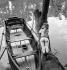 Jeune femme perchée sur un tronc d'arbre et barque sur la Marne, vers 1938-1939. © Gaston Paris / Roger-Viollet