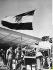 Départ de l'armée britannique de la base militaire de Shalufa. Gamal Abdel Nasser (1918-1970), homme d'Etat égyptien, rendant le drapeau britannique. Egypte, 22 mars 1955. © Ullstein Bild / Roger-Viollet