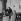 """Le réalisateur français Jacques Deray avec Jean Rochefort et Claude Dauphin, pendant le tournage de """"Symphonie pour un massacre"""". 1963. © Alain Adler/Roger-Viollet"""