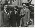 """De gauche à droite : Amedeo Modigliani (1884-1920), Pablo Picasso (1881-1973), André Salmon (1881-1969) devant le café """"La Rotonde"""". Paris (VIème arr.), 12 août 1916. Photographie de Jean Cocteau, extraite de l'ouvrage """"A Day with Picasso"""" (texte de Billy Klüver),  album de 21 photographies sur Montparnasse. Paris, musée Carnavalet. © Musée Carnavalet/Roger-Viollet"""