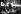 """Martin Luther King (1929-1968), pasteur américain, s''exprimant lors d''un rassemblement du """"parti démocrate de liberté du Mississippi"""" (MFDP). Derrière lui : des portraits d''Andrew Goodman, James Chaney et Michael Schwerner, militants des droits civiques assassinés par le Ku Klux Klan. Atlantic City (New Jersey, Etats-Unis), 10 août 1964. © 1976 George Ballis / Take Stoc"""