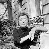 Edith Piaf (1915-1963), chanteuse française, dans un jardin. © Studio Lipnitzki / Roger-Viollet