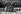 Discours du général De Gaulle pour la présentation de la Constitution de la Vème République. Paris, place de la République, 4 septembre 1958. Au pied de l'estrade, au centre :  Pierre Lefranc, son chef de Cabinet, entre deux gardes républicains. © Bernard Lipnitzki / Roger-Viollet