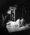 Femme étendue consultant une carte. © Roger-Viollet