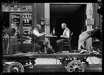 World War I. Street scene : men having lunch on truck, in front of shop of café and liqueurs. Paris, late May 1917. © Excelsior - L'Equipe/Roger-Viollet