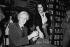 Andy Warhol (1928-1987), artiste et cinéaste américain, signant un autographe sur le bras d'une admiratrice. Londres (Angleterre), 6 novembre 1975. © PA Archive / Roger-Viollet