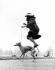 Femme sur une échasse sauteuse, promenant son chien. Photographie de Ken Russell (1927-2011).     © Ken Russell/TopFoto/Roger-Viollet