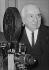 Louis Lumière (1864-1948), chimiste et industriel français, pionnier du cinéma, posant à côté d'un projecteur de films, octobre 1943. © LAPI / Roger-Viollet