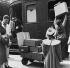 Porteur déchargeant les bagages de voyageurs sur le quai d'une gare.     © Roger-Viollet