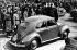 """Cérémonie de la pose de la première pierre de l'usine Volkswagen à Fallersleben, à l'occasion du 50ème anniversaire d'Aldolf Hitler. Hitler s'entretenant avec Ferdinand Porsche (1875-1951), ingénieur et construction automobile allemand, devant la voiture KdF """"La Force par la Joie"""". A leurs côtés : Dr Robert Ley (1890-1945), homme politique allemand, et Julius Schaub (1898-1967), officier allemand. Environs de Wolfsburg (Allemagne), 26 mai 1938. © Ullstein Bild / Roger-Viollet"""