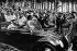 """Pose de la première pierre des usines Volkswagen près de Fallersleben. Hitler examine l'une des voitures Kdf (la """"force par la joie"""") exposées. A côté de lui, de gauche à droite Robert Ley, chef du Front du Travail, le constructeur Ferdinand Porsche, Julius Schaub, Viktor Lutze, Martin Bormann, Adolf Hühnlein et Alfred Rosenberg. © Ullstein Bild / Roger-Viollet"""