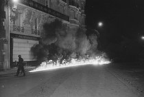 """May-June 1968 events. Burning cars at the corner of the rue Chomel and the boulevard Raspail. Paris (VIIth arrondissement), on June 11, 1968. Photograph by Bernard Charlet and Claude Poensin-Burat, from the collections of the French newspaper """"France-Soir"""". Bibliothèque historique de la Ville de Paris. © Charlet, Poensin-Burat / Fonds France-Soir / BHVP / Roger-Viollet"""